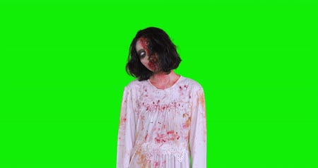 teror : Horrible zombie woman with bloody and wounded face standing against green screen background, shot in 4k resolution