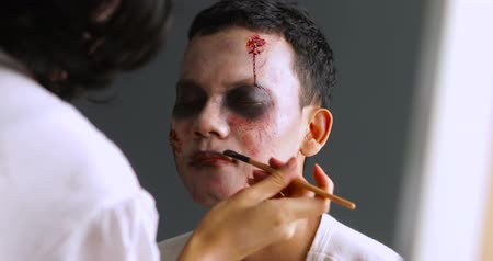 kanlı : Makeup artist preparing creepy halloween makeup on man face.Shot in 4k resolution