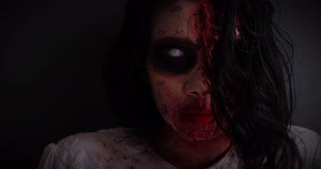make up artist : Scary zombie woman face with blood and wounds looking at the camera in dark at home, shot in 4k resolution