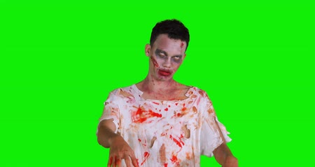 bloody hands : Scary zombie man with bloody mouth standing in the studio against green screen background. Shot in 4k resolution Stock Footage