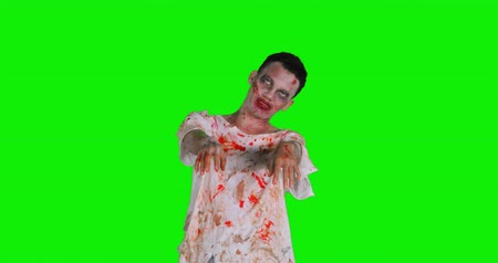 fenyegetés : Scary zombie man with bloody mouth and torn clothes in the studio, shot in 4k resolution with green screen background