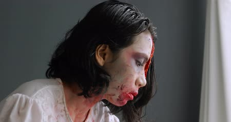 ferida : Woman applying creepy halloween makeup on her face with a brush at home. Shot in 4k resolution