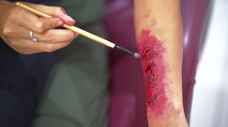 bloody hands : Woman using a brush to apply makeup special effect on hand with blood and wounds. Shot in 4k resolution