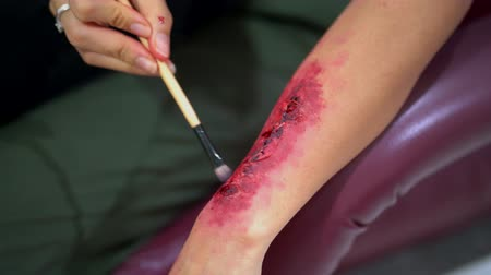 bloody hands : Closeup of woman applying halloween make up on her hand with blood, scars and wounds for halloween party. Shot in 4k resolution Stock Footage