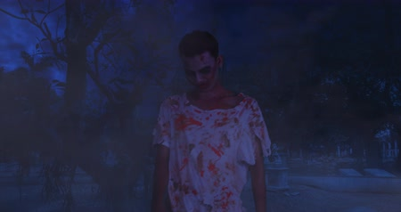 zlo : Creepy zombie man with bloody face, walking outdoors at night in dark. Shot in 4k resolution