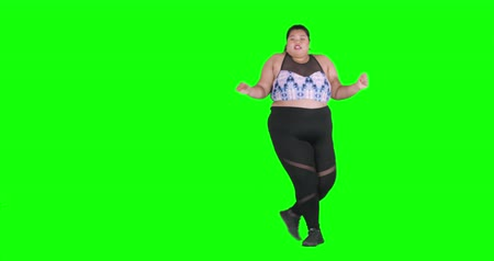 şişman : Overweight young woman dancing against green screen background while wearing sportswear in the studio, shot in 4k resolution