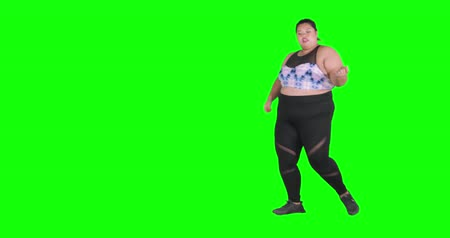 tamanho : Overweight young woman dancing in the studio while wearing sportswear, shot in 4k resolution with green screen background