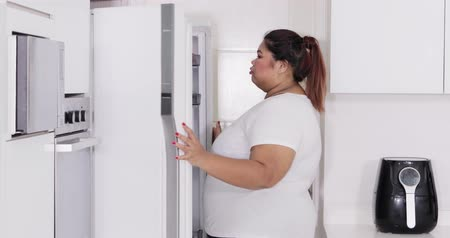 ataque : Overweight young Asian woman opening refrigerator to seek some snack in the kitchen at home. Shot in 4k resolution Vídeos