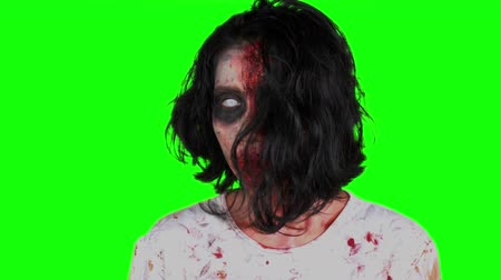 yara : Scary zombie woman face with bloody mouth and white eye looking at the camera in the studio. Shot in 4k resolution with green screen background Stok Video