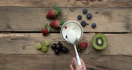 yoghurt : Stop motion of hand taking yogurt with spoon in a glass over wooden table. Shot in 4k resolution