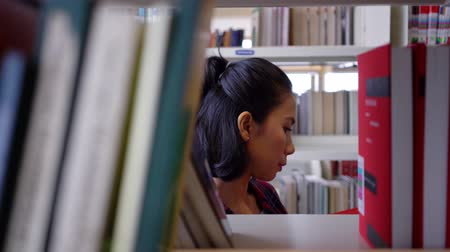 könyvesbolt : Young asian woman taking a book from library bookshelf and read the book in the library aisle. Shot in 4k resolution Stock mozgókép