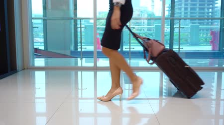 dragging : Young business woman legs walking in train station while carrying a luggage. Shot in 4k resolution Stock Footage