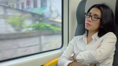 выражать : Young business woman sitting next the window and sleeping in the airport train. Shot in 4k resolution