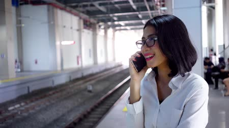 платформа : Young business woman standing on the train station platform while speaking with a mobile phone and looking at her wristwatch. Shot in 4k resolution