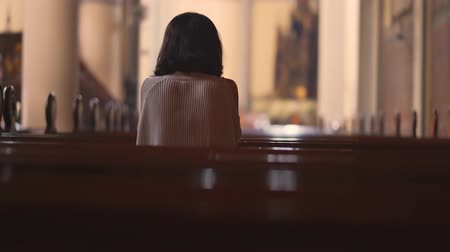 övgü : Back view of a young Christian woman sitting in the church while praying to the GOD. Shot in 4k resolution