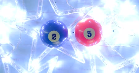 sinuca : Flat lay two billiard balls with number 25 and glowing Christmas star on wooden background. Shot in 4k resolution
