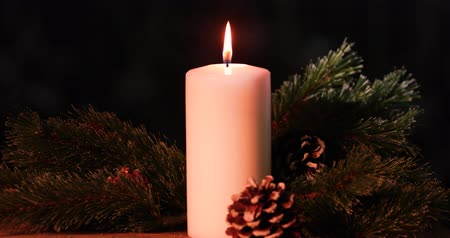 сверкающий : Burning Christmas candle with pine cones and fir tree on dark background. Shot in 4k resolution