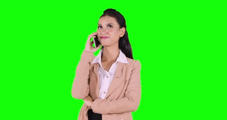 indonéz : Young business woman making a phone call while standing in the studio with green screen background. Shot in 4k resolution
