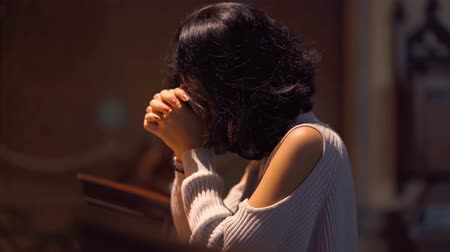 louvor : Christian woman praying to GOD while sitting in the church with clasped hands. Shot in 4k resolution