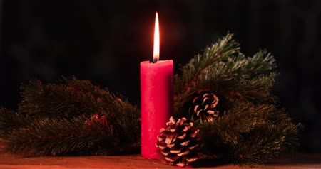 feliz natal : Burning red Christmas candle on wooden table with pine cones and fir tree. Shot in 4k resolution with dark background