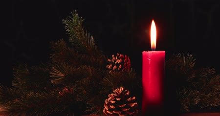 сосновая шишка : Burning red Christmas candle with fir tree and pine cones on dark background. Shot in 4k resolution Стоковые видеозаписи