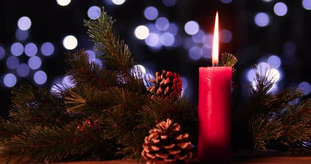 feliz natal : Christmas decoration with burning candle, pine cones, and fir branches on wooden table. Shot in 4k resolution with blurred lights background