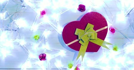 table top shot : Flay lay Christmas gift shaped heart symbol with glowing Christmas star and bells on wooden background. Shot in 4k resolution Stock Footage