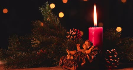 heykelcik : Christmas nativity scene with figurine of baby Jesus, candle, pine cones, and fir branches. Shot in 4k resolution with blurred lights Stok Video