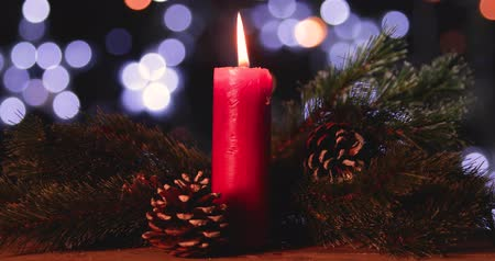 presentes : Glowing Christmas candle with pine cones and fir tree on wooden table. Shot in 4k resolution with blurred shiny lights background