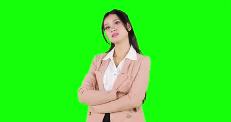 сложены : Modern business woman smiling at the camera while standing in the studio with folded hands. Shot in 4k resolution with green screen background Стоковые видеозаписи