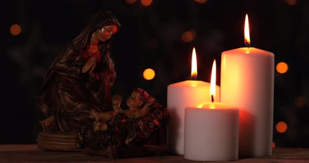 jesus born : Nativity scene of baby Jesus with Mary and burning candles on blurred twinkling lights background. Shot in 4k resolution