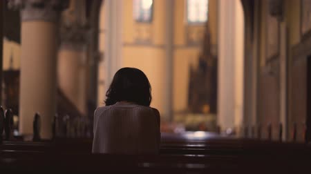 louvor : Rear view of a young Christian woman praying to GOD while sitting in the church. Shot in 4k resolution