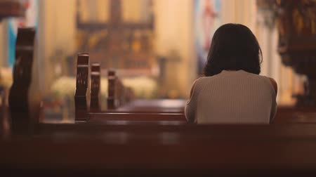 övgü : Back view of religious Christian woman sitting in the church while praying to GOD. Shot in 4k resolution
