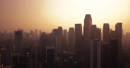 sudirman : JAKARTA, Indonesia - October 04, 2018: Aerial footage of Jakarta skyline at dusk with silhouette of skyscrapers from a drone flying down. Shot in 4k resolution