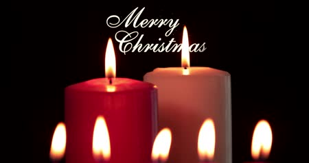 mumlar : Merry Christmas text and bright candles light on dark background. Shot in 4k resolution