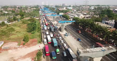 toll : West Java, Indonesia - October 03, 2018: Aerial view of cars on the traffic jam in Jakarta-Cikampek toll road with columns of elevated toll road project. Shot in 4k resolution Stock Footage