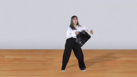 aktatáska : Happy Asian business woman holding a briefcase and dancing in the studio. Shot in 4k resolution Stock mozgókép
