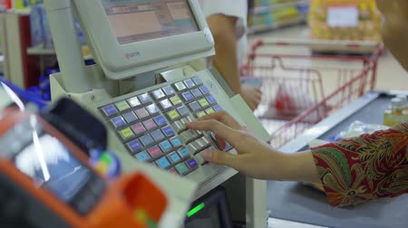 регистр : JAKARTA, Indonesia - October 10, 2018: Cashier hand registering orders on the cash register machine in the supermarket shop. Shot in 4k resolution