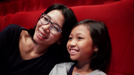 азиатский : Happy little girl and her mother watching movie in the cinema theater. Shot in 4k resolution