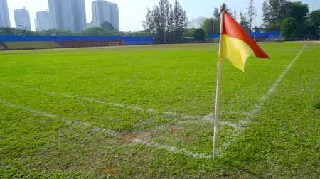 turf : JAKARTA, Indonesia - October 10, 2018: Slow motion of red and yellow corner flag in empty soccer field with white line and green grass. Stock Footage