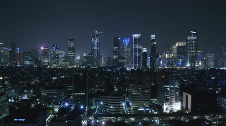backwards : JAKARTA, Indonesia - October 15, 2018: Aerial view of Jakarta skyscrapers in central business district with beautiful lights at night. Shot in 4k resolution