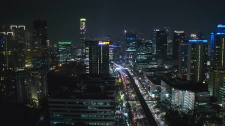 központi : JAKARTA, Indonesia - October 15, 2018: Beautiful night aerial view of Jakarta city with skyscrapers view and night traffic. Shot in 4k resolution
