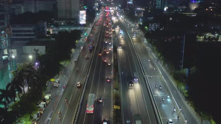 toll : JAKARTA, Indonesia - October 16, 2018: Aerial scenery of night traffic on the Jakarta tollway with light trails of moving vehicles. Shot in 4k resolution