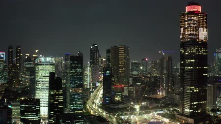 central business district : JAKARTA, Indonesia - October 16, 2018: Aerial view of Jakarta city with skyscrapers and beautiful night lights at night. Shot in 4k resolution