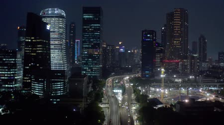 passagem elevada : JAKARTA, Indonesia - October 19, 2018: Beautiful aerial view of skyscrapers and overpass road with night light in Jakarta city, Indonesia. Shot in 4k resolution Vídeos