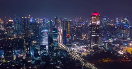 central business district : JAKARTA, Indonesia - October 23, 2018: Beautiful aerial hyperlapse in Jakarta city with skyscrapers and highway at nighttime. Shot in 4k resolution