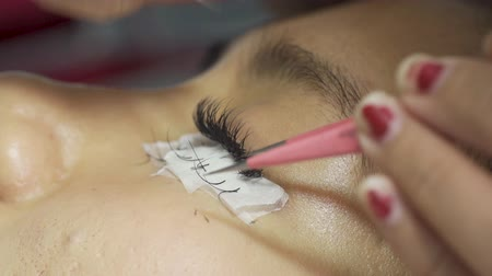 pinça : Eyelashes of a young woman getting eyelash extension treatment in a beauty salon. Shot in 4k resolution Vídeos