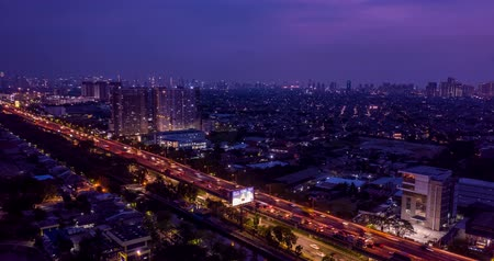 toll : JAKARTA, Indonesia - October 30, 2018: Beautiful hyperlapse of toll road of Wiyoto Wiyono with light trails of moving vehicles at night in Jakarta, Indonesia. Shot in 4k resolution