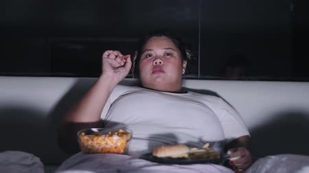 nezdravý : Obese woman eating junk foods on the bed at nighttime before sleep at home. Shot in 4k resolution