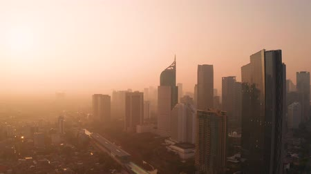 distrito financeiro : JAKARTA, Indonesia - October 30, 2018: Beautiful aerial scenery of silhouette of skyscrapers on misty morning at sunrise time in Jakarta, Indonesia. Shot in 4k resolution